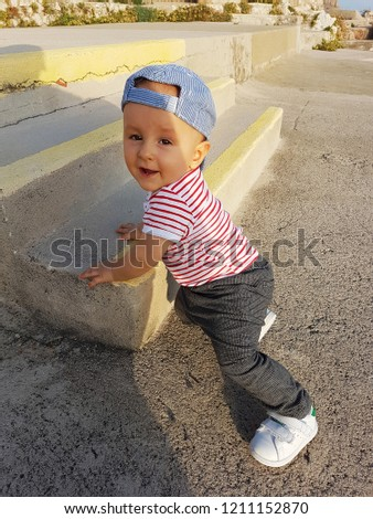 Cute Baby Boy 1 Year Wearing A Cap Backwards And Striped Clothes, Close Up Portrait, Baby Standing On The Stairs