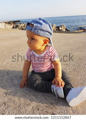 Cute Baby Boy 1 Year Wearing A Cap Backwards And Striped Clothes, Close Up Portrait. Mediterranean Sea In The Background
