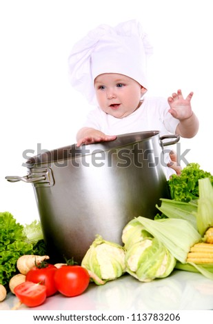 Cute baby chef with big pot and vegetables over white background