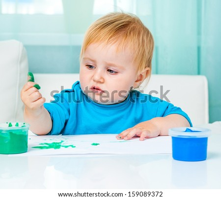 cute baby    draw finger paints at home in bright living room
