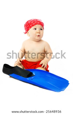 cute baby dressed in summer clothes sitting on the floor with blue flippers