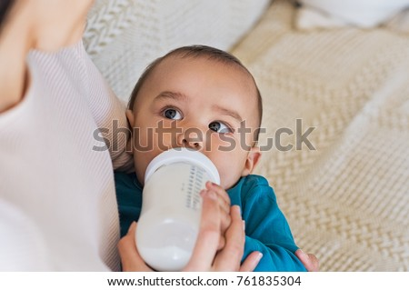 Cute baby drinking milk from baby bottle while looking his mom. Mother feeding son infant from bottle. Little boy drinking milk from bottle at home.