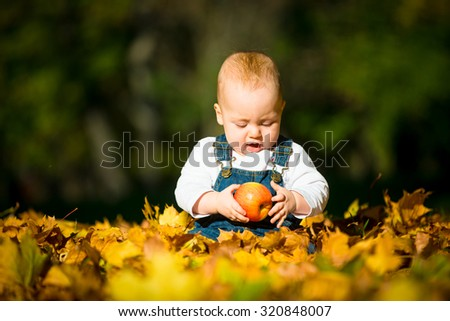 Cute baby eating apple outdoor in fall sunny day - sitting in leaves