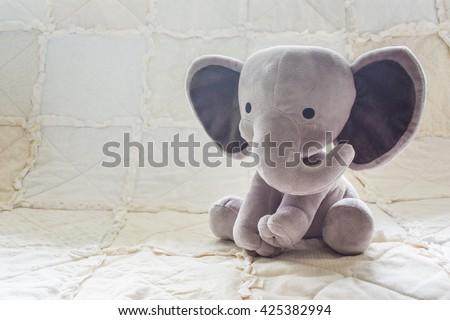 Cute Baby Elephant Stuffed Animal on a White Quilt