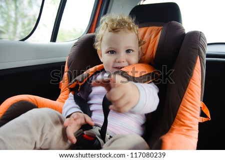 Cute baby  enjoying a road trip in a baby car seat
