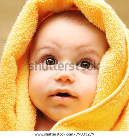 Cute baby face wrapped in towel, hygiene and health care concept