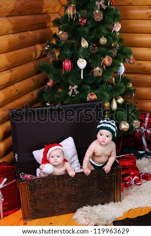 Cute baby girl and baby boy in xmas hats inside large chest
