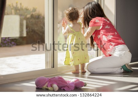 Cute baby girl and her mother looking outside through a glass door