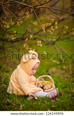 cute baby girl at bunny costume with easter cake and willow outdoor