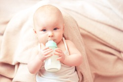 Cute baby girl drinking milk from glass bottle in bed. Healthy nutrition for newborns. Childhood.