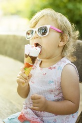 Cute baby girl eating ice cream outdoor.