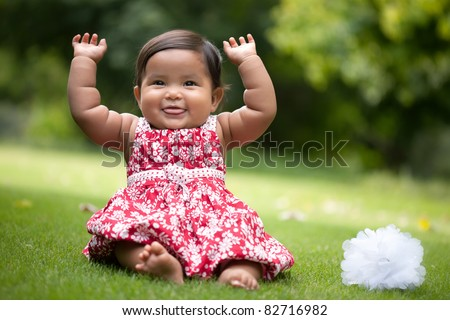 cute baby girl gesturing with her arms up and blowing raspberries