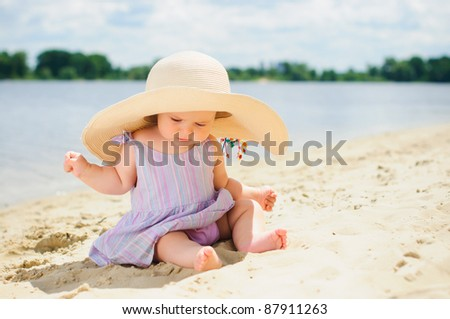 cute baby girl in a beige hat sitting and playing on the beach with sand.
