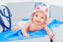 Cute baby girl in a sun hat laying on a beach lounge chair