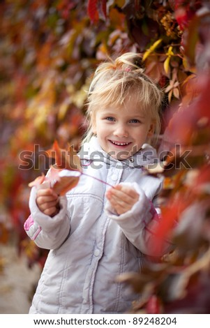 Cute baby girl in autumn leaves