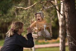 Cute baby girl in bonnet cap is swinging on a wooden swings and her grandmother is playing with her and they are laughing. Image with selective focus and toning