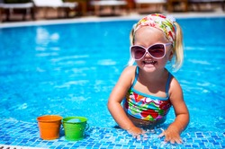 Cute baby girl in sunglasses playing with toys in the swimming pool outdoors