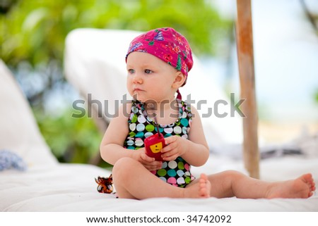 Cute baby girl in swimsuit relaxing by the pool