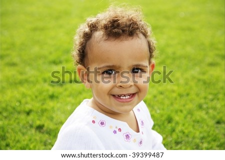 cute baby girl laughing on green grass
