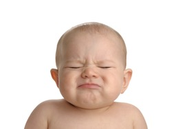 Cute baby girl makes a funny upset face isolated on a white background.