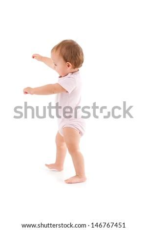 Cute baby girl making first steps, balancing.