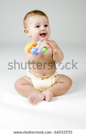 Cute Baby Girl Playing with a Toy in Diaper.