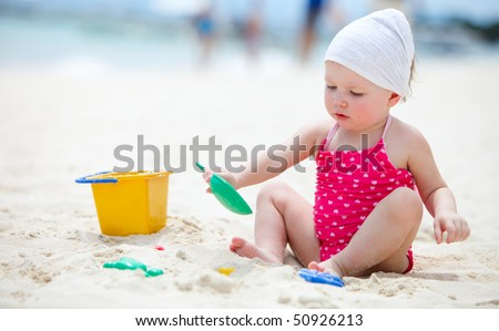 Cute baby girl playing with beach toys on tropical beach