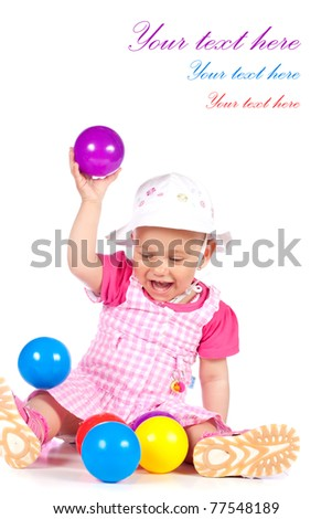 Cute baby girl playing with colorful balls in studio isolated over white background