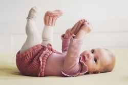 Cute baby girl playing with her sock, wearing dusty pink crochet bloomer and socks, smiling looking at camera, lying in bed
