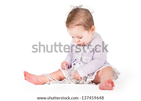 Cute baby girl playing with pearls