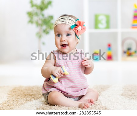 cute baby girl playing with toy indoors stock photo