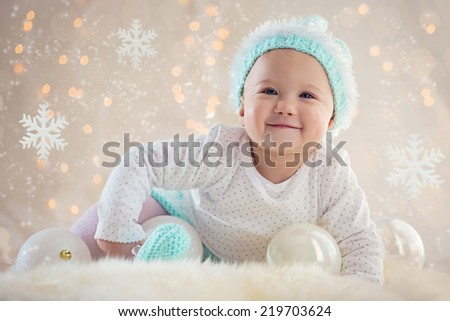 Cute Baby girl posing and smiling with Christmas snowflake ornaments and balls
