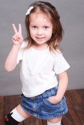 Cute baby girl posing in studio, wearing jeans skirt and white shirt
