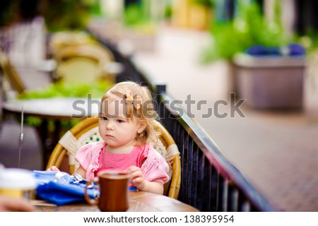 Cute baby girl sitting in european outdoor cafe at sunny summer day near table and waiting
