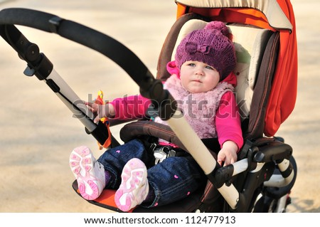 cute baby girl sitting in stroller - stock photo