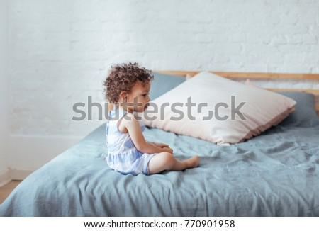 Cute baby girl sitting on bed. #770901958