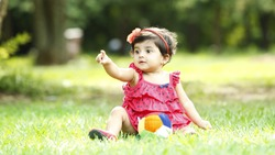 Cute baby girl sitting on the grass in the park