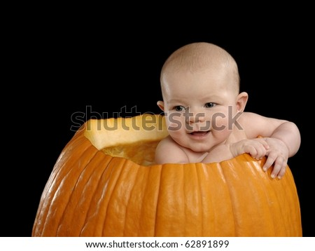 Cute baby girl smiling in a pumpkin for her first halloween, isolated on a black background