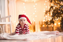 Cute baby girl wearing santa claus suit crawling on floor over Christmas lights. Looking at camera. Holiday season.