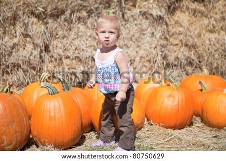 Cute baby-girl with big orange pumpkins - stock photo