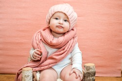 Cute baby girl with blue eyes in a pink knitted hat and scarf on a pink background. The concept of a cozy warm winter or spring