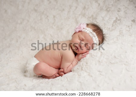 Cute baby girl with feet crossed sleeping on a white lace blanket