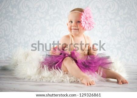Cute baby girl with flower headband and pearls