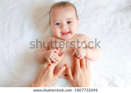 Cute baby holding mother hands while his mom making belly and body massage for him. Mixed race Asian-German infant relaxing with smiling face.adorable boy massaging after bathing.