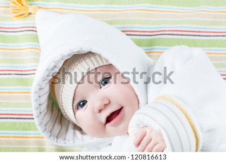 Cute baby in a funny hat on a colorful blanket