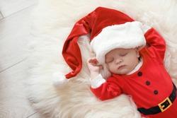 Cute baby in Christmas costume sleeping on fur rug