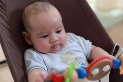 Cute baby infant spitting saliva while playing with toy at home. Mixed race Asian-German newborn two months old.