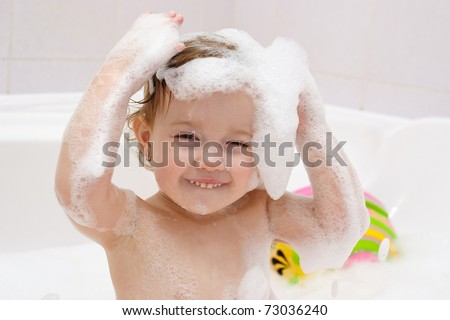 Cute baby is washing her hair in bath. The symbol of purity and hygiene education