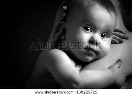 cute baby looking at hands of the mother in an embrace, monochrome