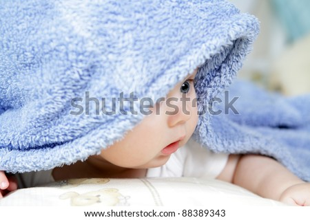 cute baby looking out from under blanket